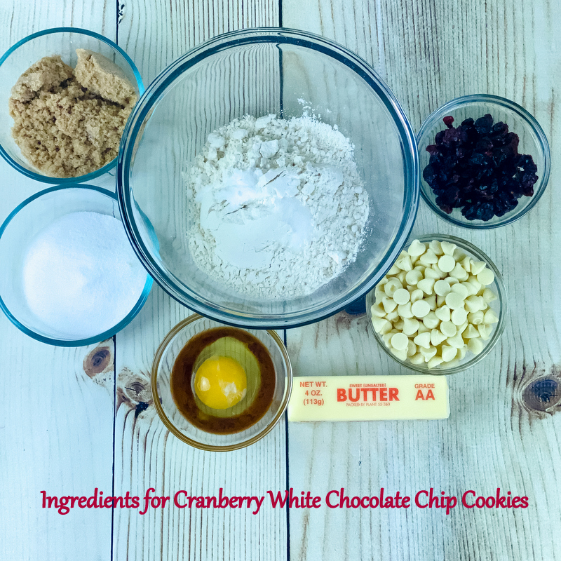 Bowls of brown and white sugars, flour, egg and vanilla, cranberries and white chocolate chips with a stick of butter