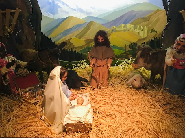 Nativity scene with a woman kneeling by a baby in a manger