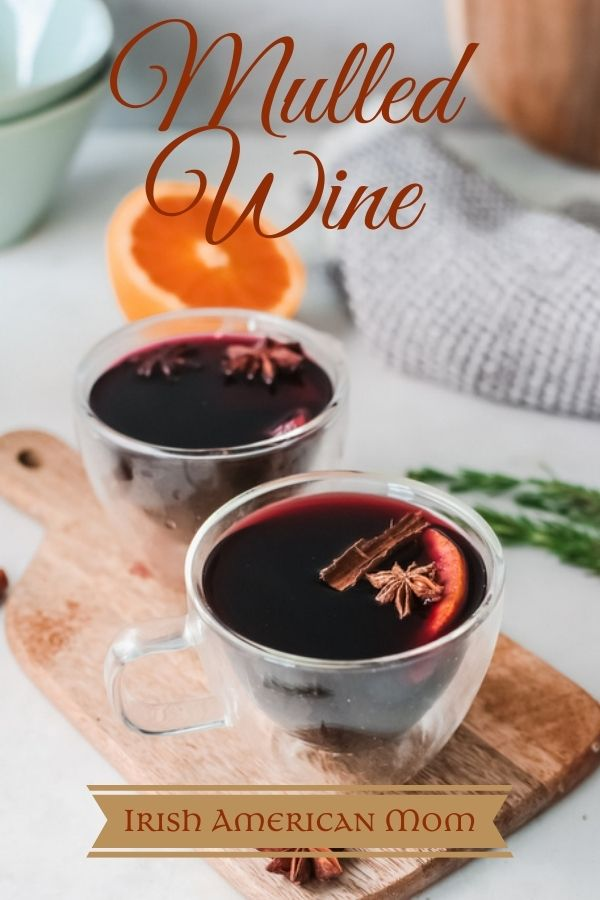 Glasses of mulled wine on a wooden cutting board beside half an orange