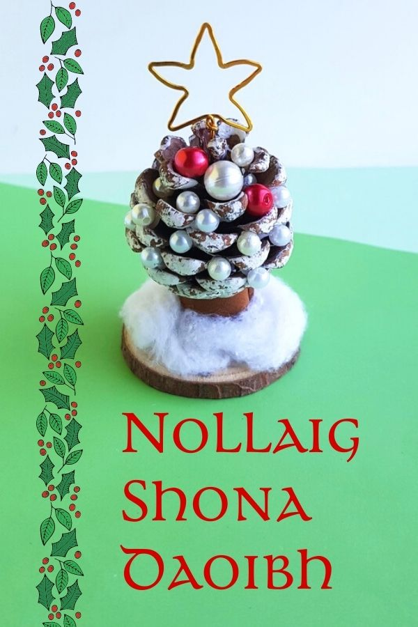 A pine cone Christmas tree on a wooden circle with a holly border and text on a graphic