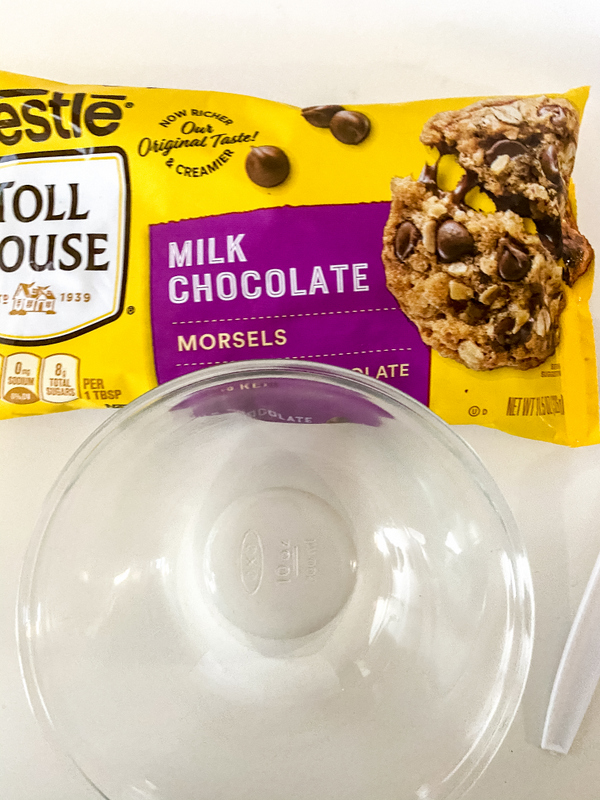 A yellow packet of chocolate chips with a picture of a chocolate chip cookie and text beside a glass bowl