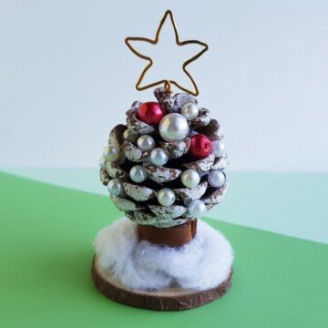 A pine cone Christmas tree on a small wooden circle on a green surface