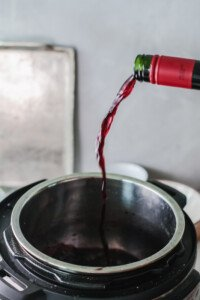 Pouring a bottle of red wine into a pressure cooker pot