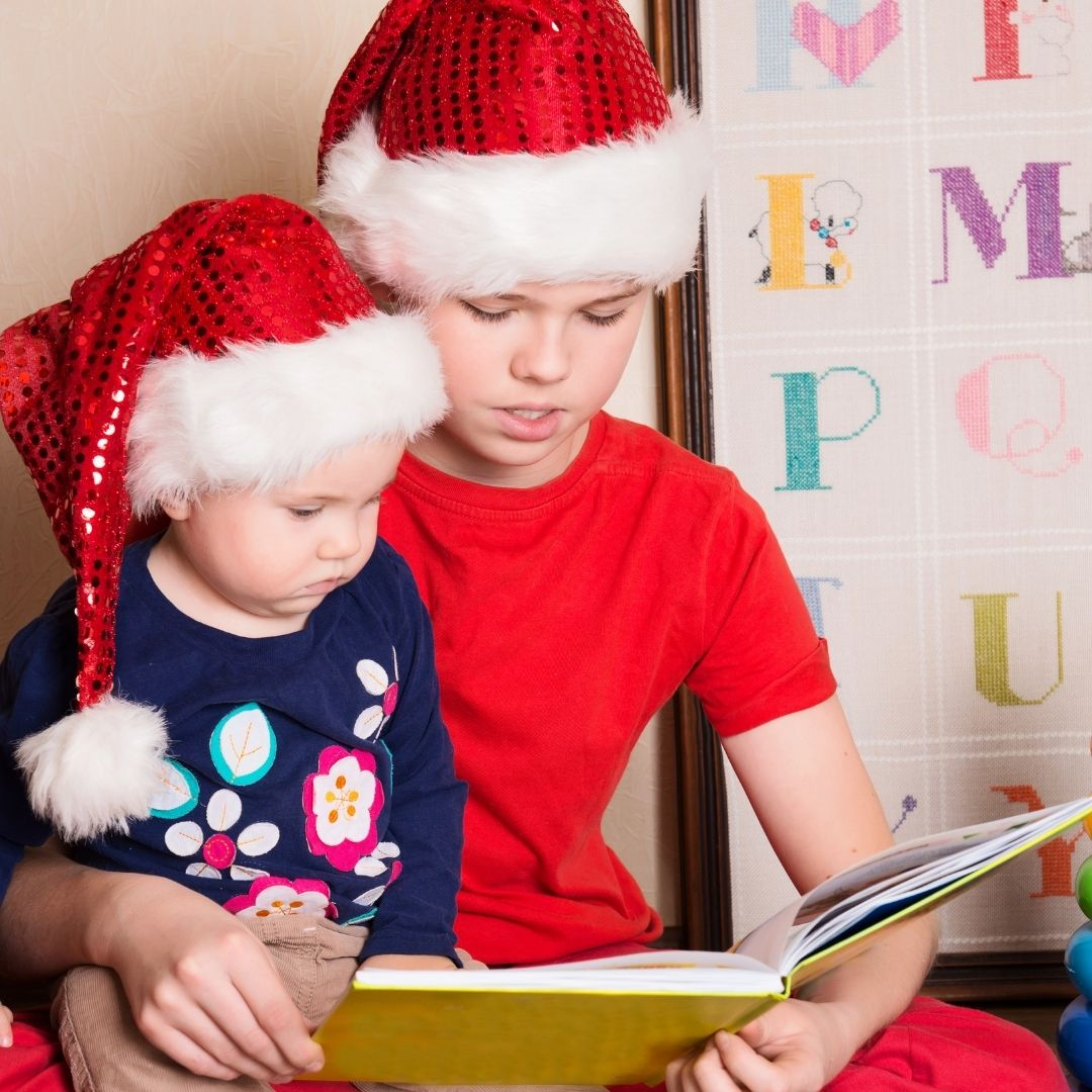 Two boys wearing Christmas hats reading together