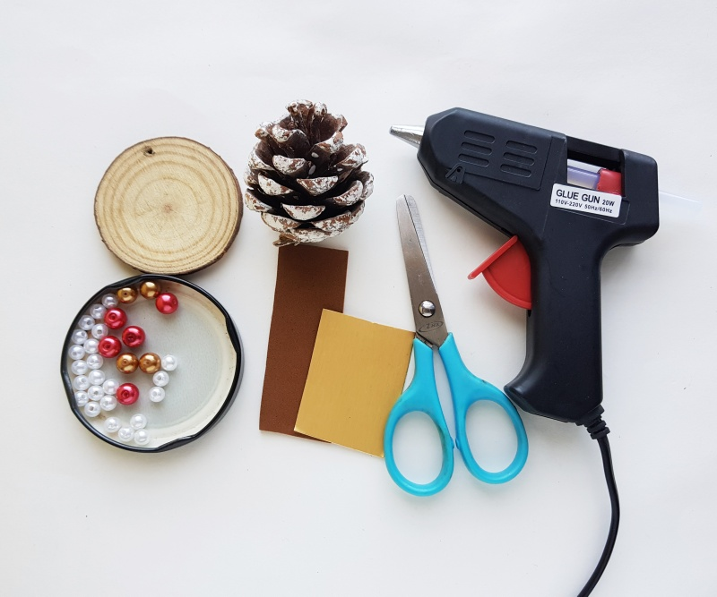 Heat gun, scissors, card foam, beads in a jar lid, a wooden disc, and a pine cone displayed on a white surface