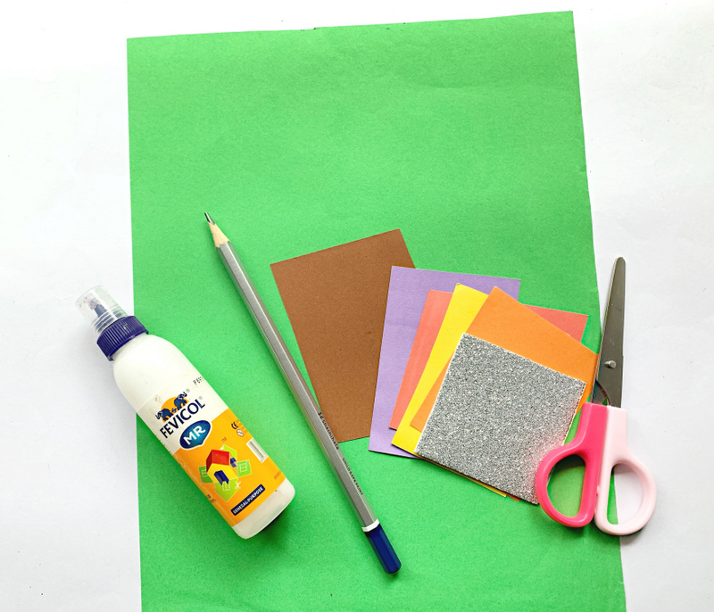 Green sheet of paper with small square cuttings of brown, purple, yellow, orange and glitter paper bside a scissors, a pencil and glue