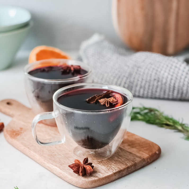 Red mulled wine in two glass cups on a wooden cutting board