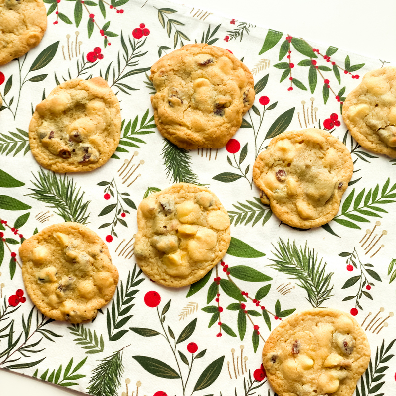 A collection of cranberry and white chocolate chip cookies on a green and red floral placemat