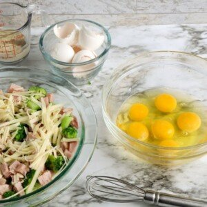 Six cracked eggs in a glass bowl, beside egg shells in a bowl and a pie dish of ham and cheese and broccoli