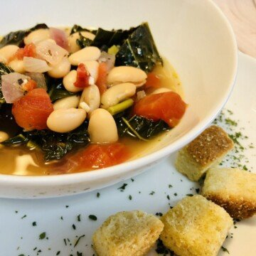 Diced tomato, white beans, kale and onions in broth in a white bowl