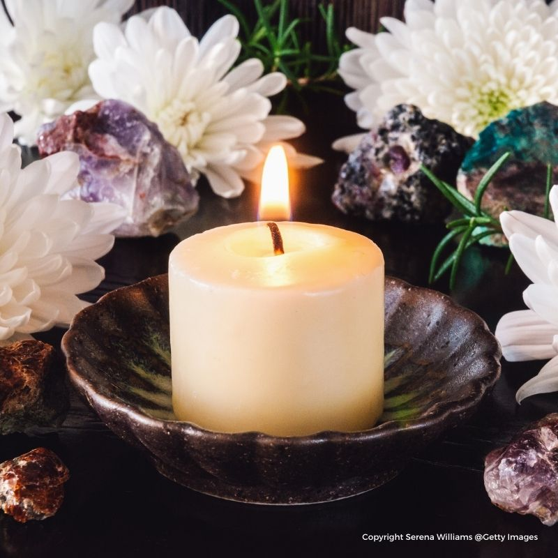 A lit candle in a black dish surrounded by white flowers