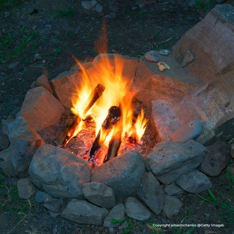 A fire burning in a stone fire pit