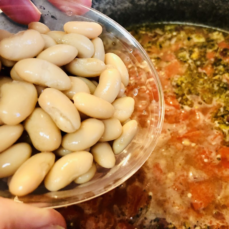 White beans being held in a glass bowl over a pot of soup.