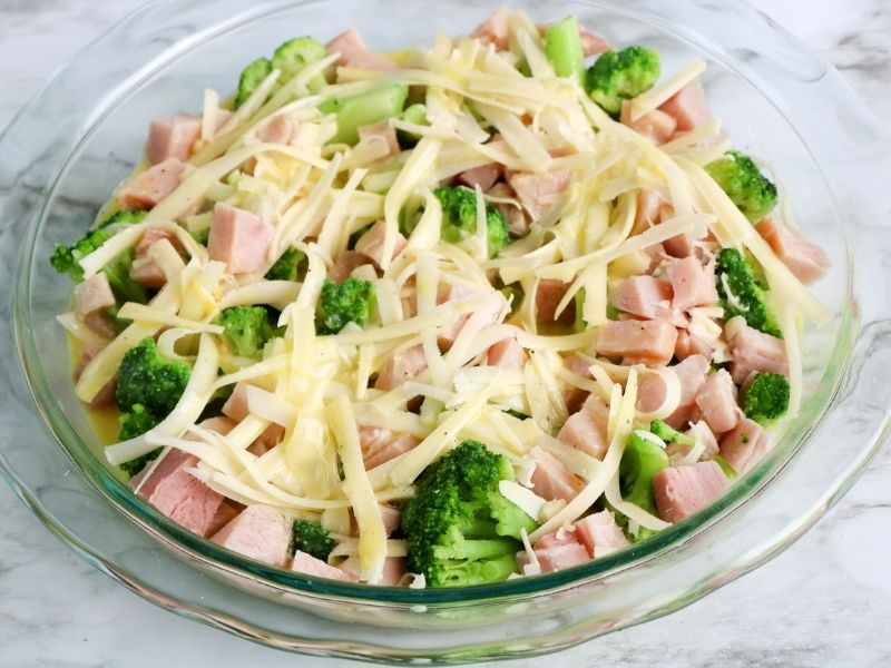A glass pie dish with ham, broccoli and grated cheese