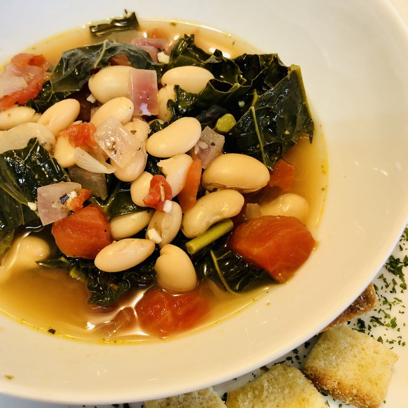 Aerial shot of a white bowl with vegetable soup with beans, kale, onions and tomatoes in broth beside croutons