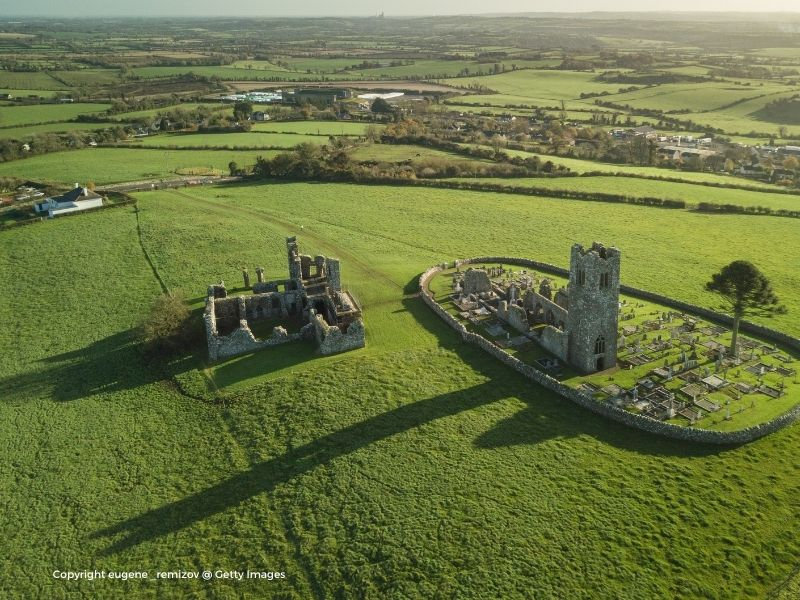 Aerial view of stone monastic buildings and a tower in ruins in the middle of a green field
