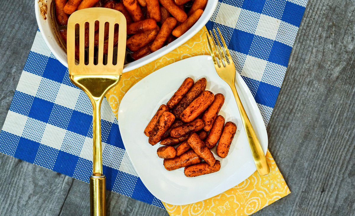 Carrots on a plate with golden silverware and spatula on a blue check place mat
