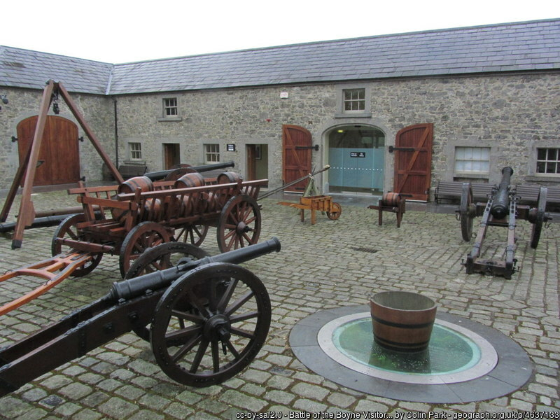 Cannons and old wagons in a cobblestone square surrounded by stone buildings