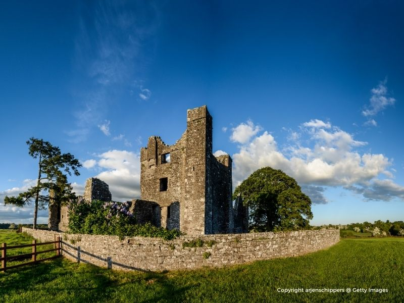Ruined stone castle under a blue sky and surrounded by a stone wall