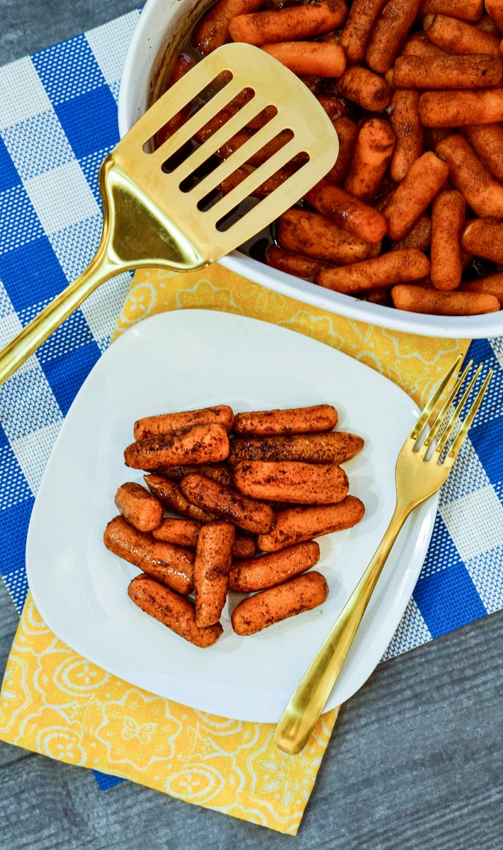 A serving of carrots on a plate beside a casserole dish of glazed carrots