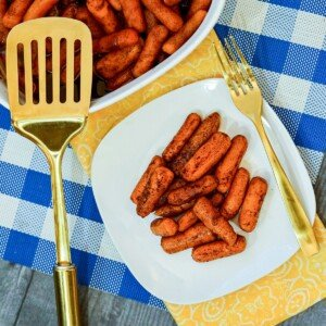 Baby carrots on a white plate displayed beside a casserole of baked carrots