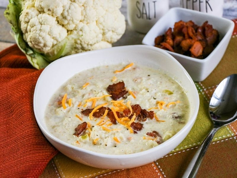 A bowl of cauliflower soup with bacon bits displayed beside a head of cauliflower