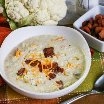 Bacon bits on a bowl of cauliflower soup beside a bowl of bacon bits and a head of cauliflower