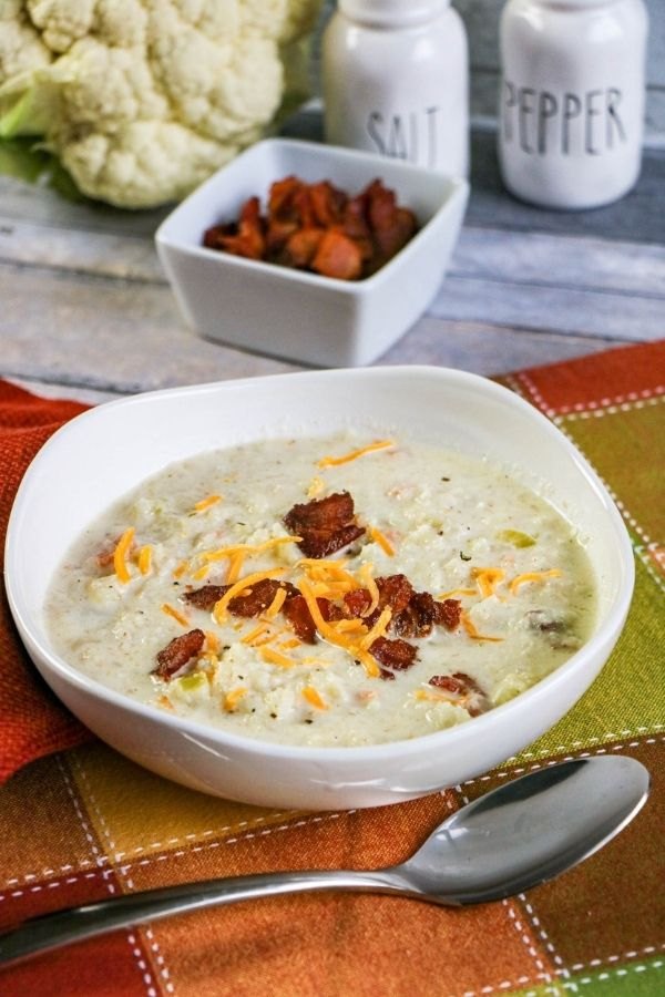 A bowl of white soup with bacon bits and grated cheese beside a spoon