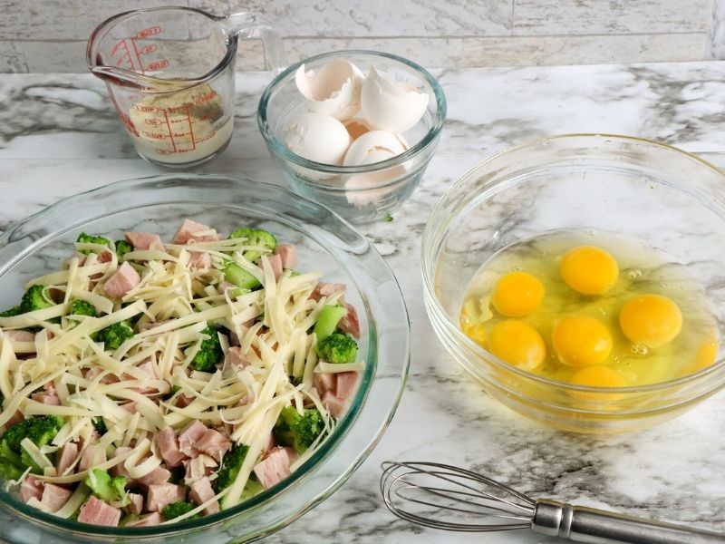 Cheese, broccoli and ham in a pie dish beside a bowl of cracked eggs, egg shells and a pitcher of milk and seasonings