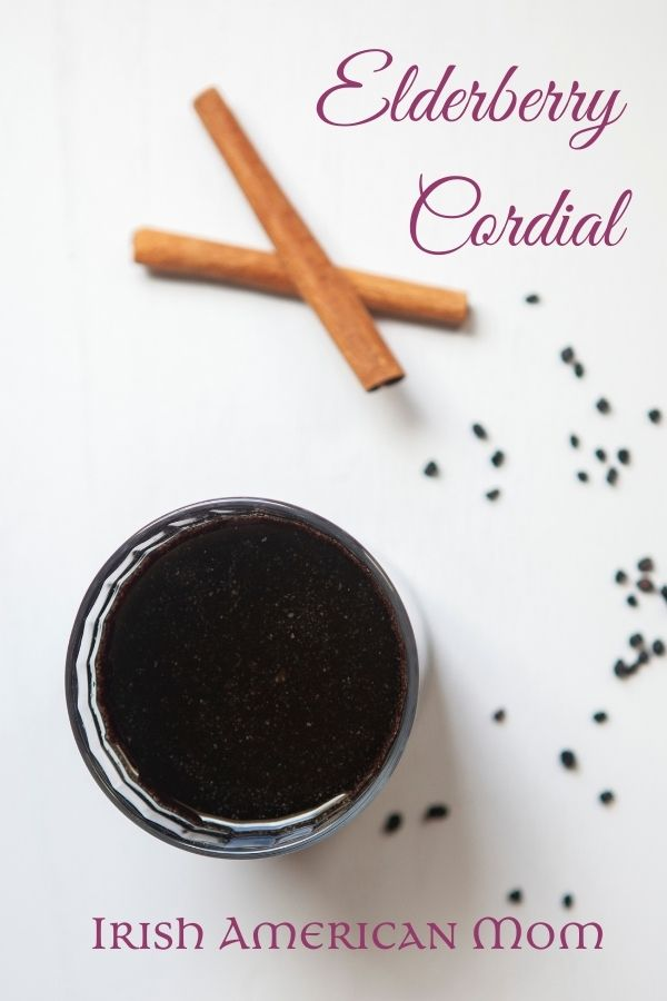 An aerial view of a glass of elderberry cordial beside cinnamon sticks and scattered dried berries