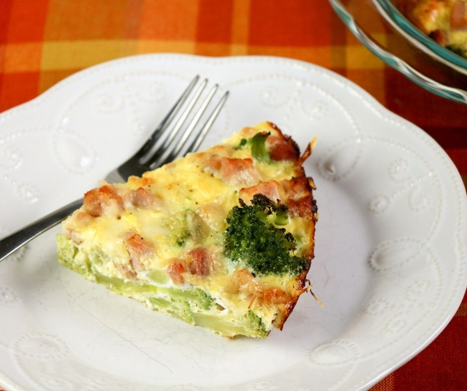 A slice of quiche with ham and broccoli on a white plate with a silver fork