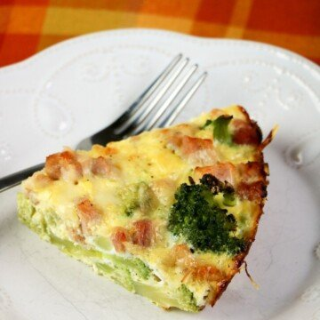 Slice of crustless quiche on a white plate with a fork