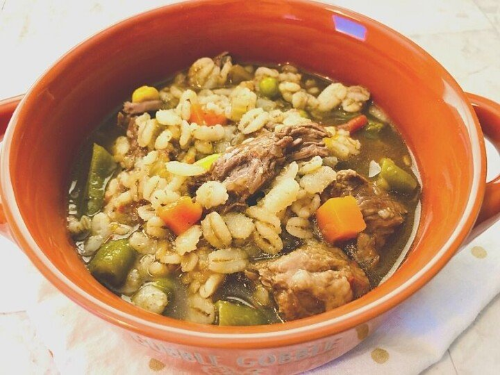 A bowl of beef stew with barley and vegetables
