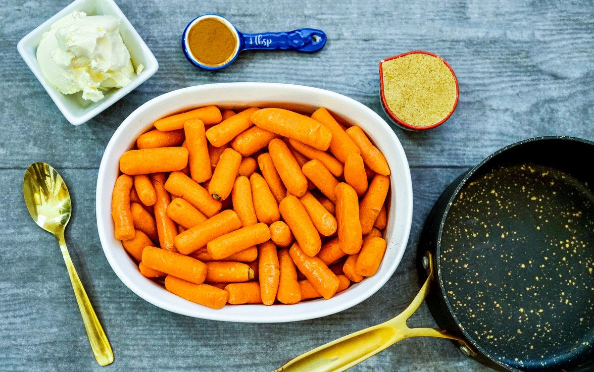 Bowls of butter, carrots, brown sugar and a spoon of cinnamon beside a black skillet