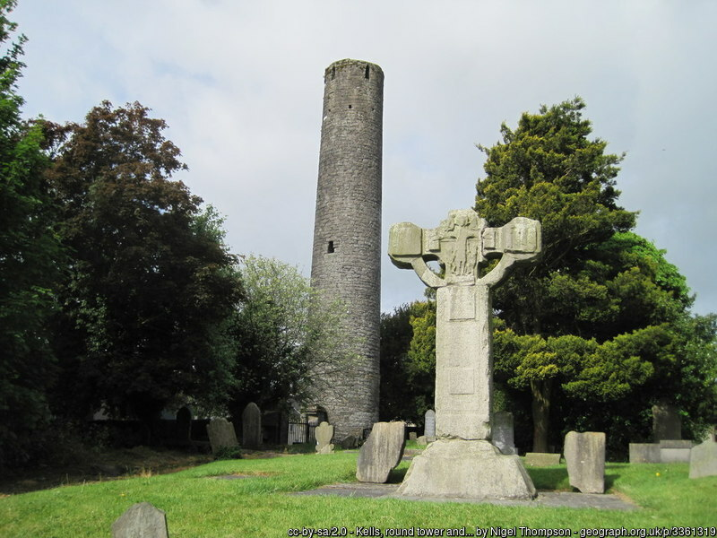 A stone tower and broken stone cross in green grass and surrounded by trees