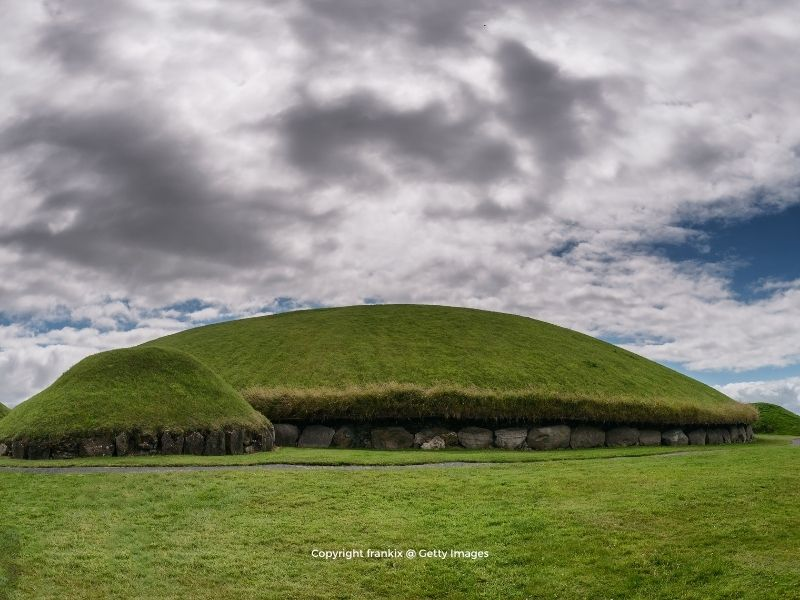 Earthen burial mounds with green grass growing on top