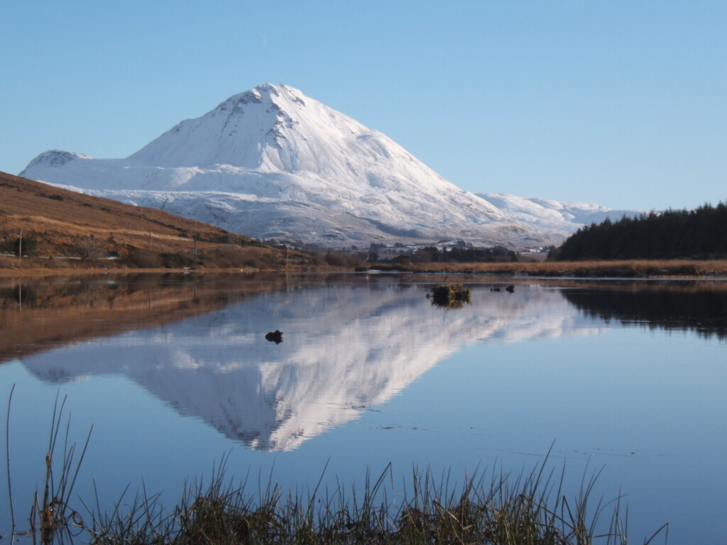 A snow capped peak reflecting in a lake