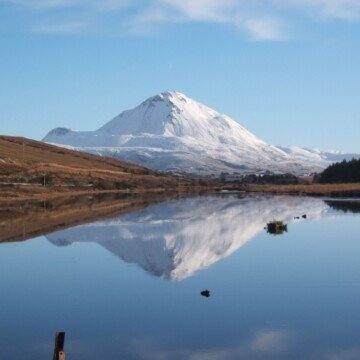 A snowy mountain reflecting in a lake under a blue sky