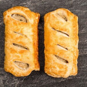 Two puff pastry sausage rolls on a black slate