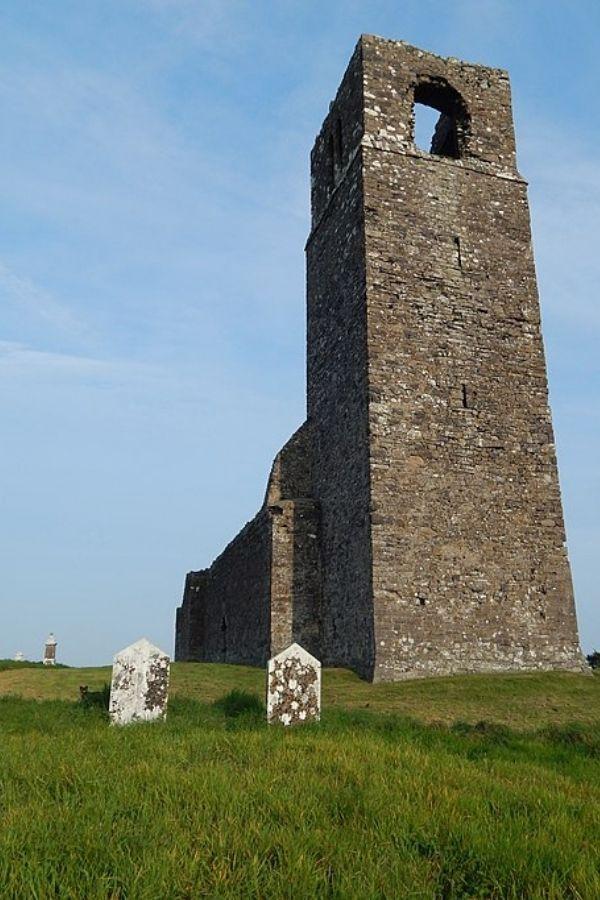 Stone steeple in a green field beside headstones