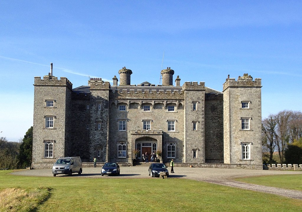 A large stone castle with grass and cars in front