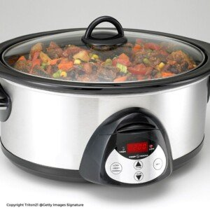 A black and silver slow cooker with stew