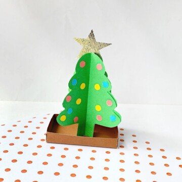 Green paper Christmas tree on a brown card base displayed on red and white polka dot pattern