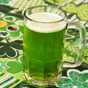 Glass with a handle full of green beer on a shamrock cloth