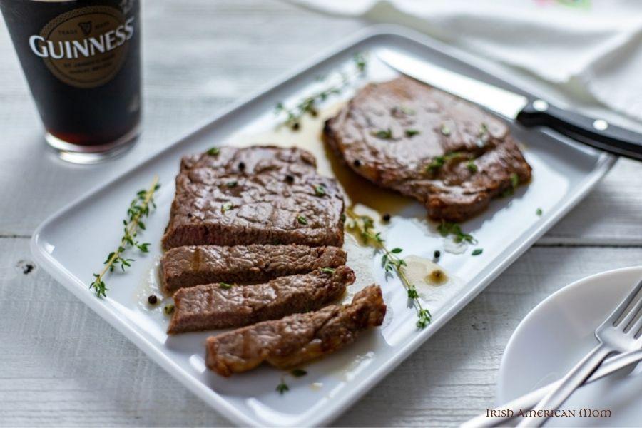 Steaks on a platter beside a pint of Guinness stout