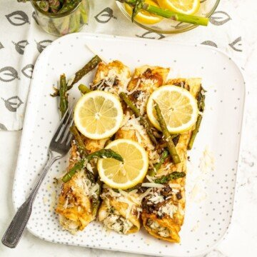 Asparagus and chicken pancakes on a plate with lemon slices as garnish