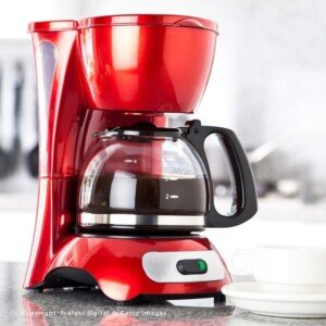 Red coffee maker with a jug of brewing coffee