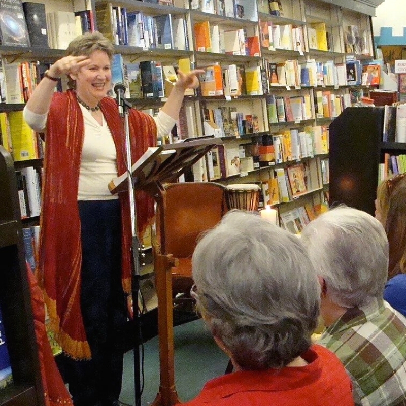 A woman at a lectern teaching a class in a book store