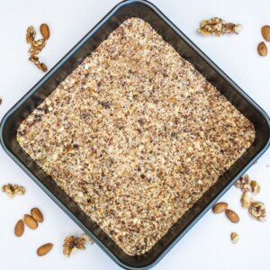 Baking pan with a layer of ground nuts and some scattered walnuts on a counter top