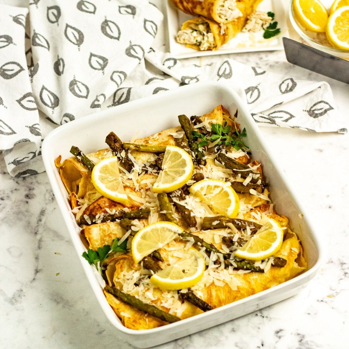 Casserole with stuffed crepes, asparagus and lemon slices